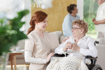 senior woman drinking her tea while talking to her caregiver