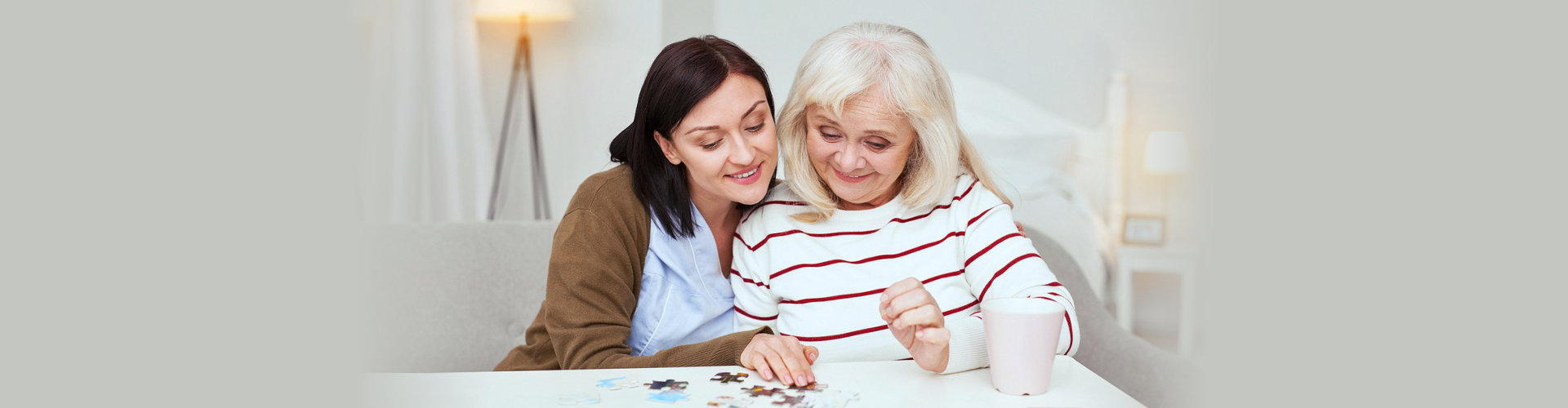 caregiver and senior woman playing with puzzles